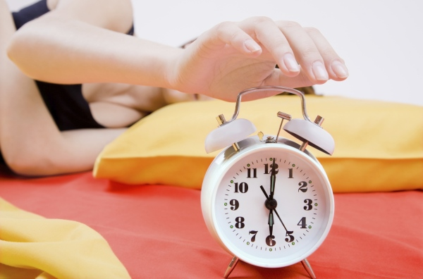 Young adult girl switching off alarm clock