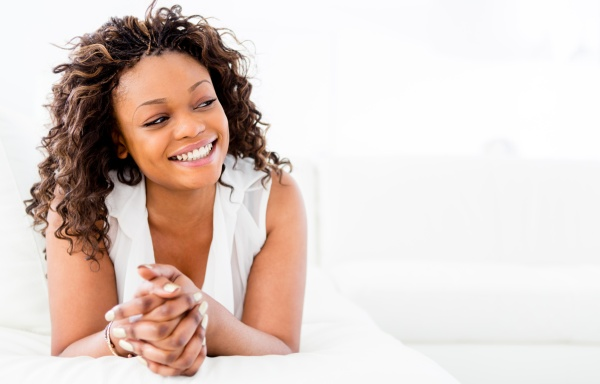 Black woman looking very happy laughing at home
