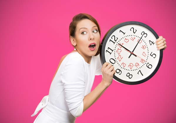 Closeup portrait woman, worker, holding clock looking anxiously, pressured by lack, running out of time, isolated pink background. Human face expression, emotion, reaction, corporate life style