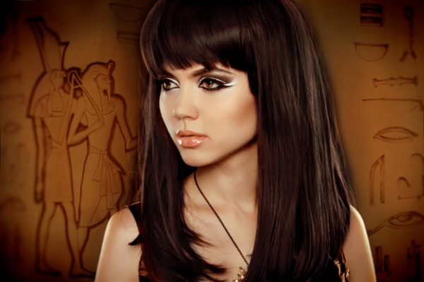 Hair. Beautiful Brunette Girl over Egyptian hieroglyphs