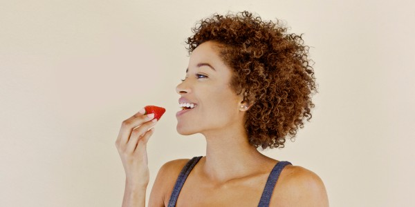 Young woman eating an organic strawberry
