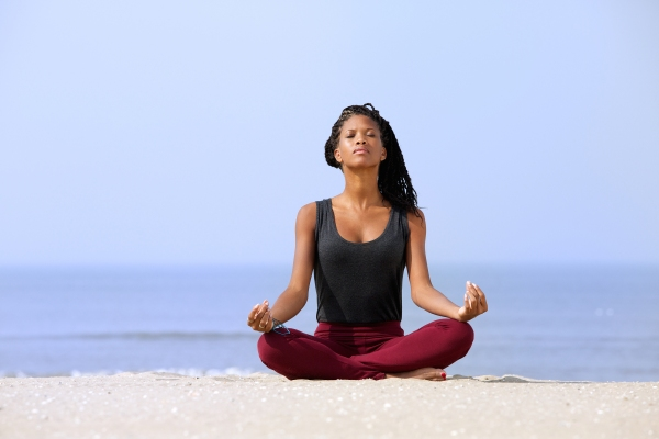 Portrait of a beautiful young woman sitting in yoga pose at the beach